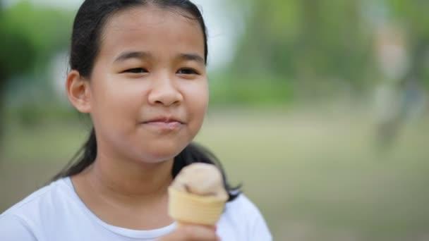 Asijské dospívající jíst zmrzlinu s štěstí tváří