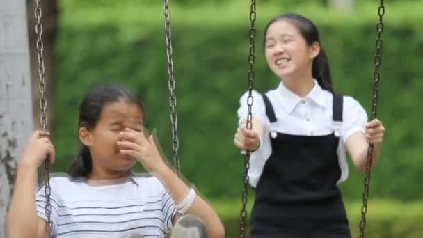 two asian teenager playing on swing in public park