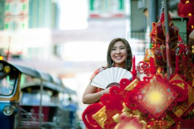 asian woman wearing chinese tradition clothes with chinese  bamboo fan toothy smiling face in yaowarat street china town of bangkok thailand