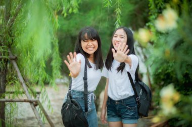 portrait of two asian teenager relaxing with happiness in green park