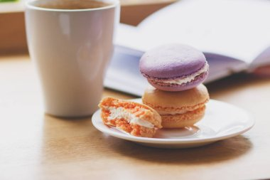French colored macarons on the plate and a cup of coffee, soft focus background