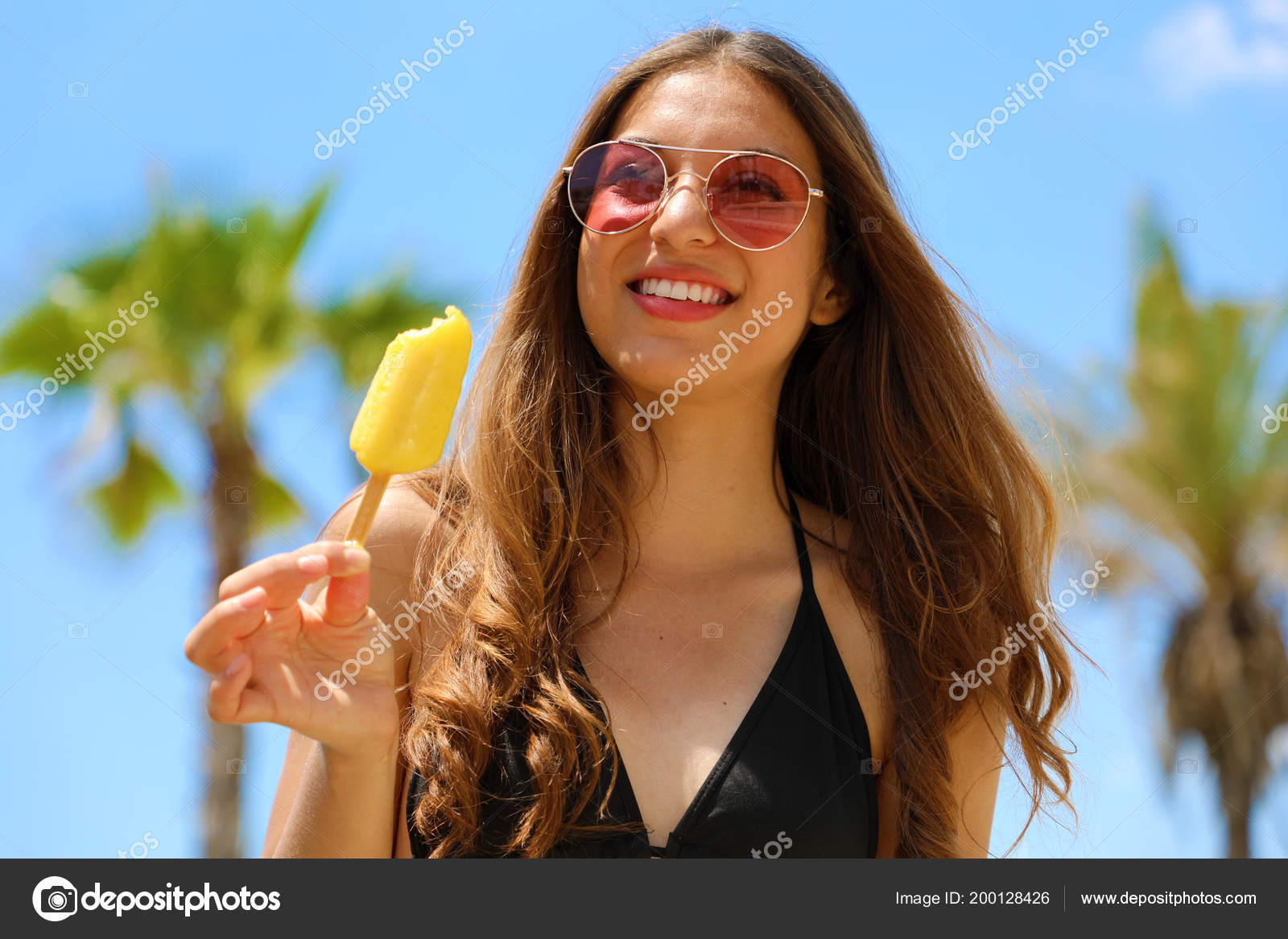 702443894f3 Happy beautiful girl with sunglasses on the beach eating ice lolly with  palm trees on the backgroud. Summer holidays concept. — Photo by sergio pulp