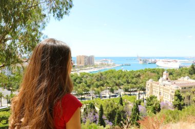 Rear view of girl looking at Malaga sight with the city hall on the right, Gibralfaro viewpoint, Malaga, Spain