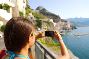 Holidays in Italy! Beautiful young woman take picture with smart phone of Atrani village on Amalfi Coast, Italy