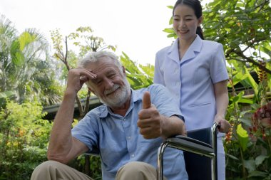 senior man happiness sitting on wheelchair with smiling nurse, t