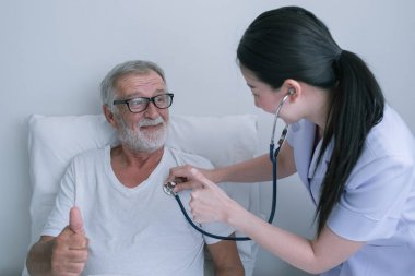 senior man with smiling nurse, takes care and discussion after h