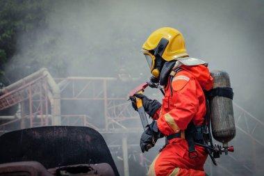 İtfaiyeci güvenlik süiti giyiyor ve yangın söndürme dumanı ve yangın güvenliği kavramı ile yangın hasarına doğru yürüyor.