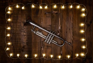 trumpet on wooden background with light bulbs
