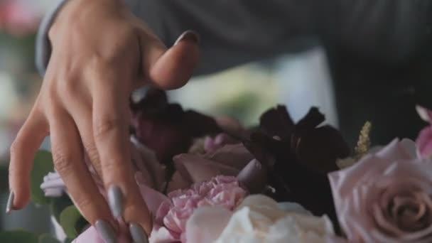 Uzavření rukou ženského květinářství aranžuje Iris, lidi, hydratální květiny, eukalytus pro kytici v květinářství