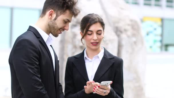 Business people using a mobile phone in front of their office
