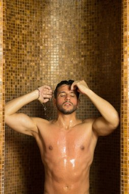 Handsome man doing a shower in a spa