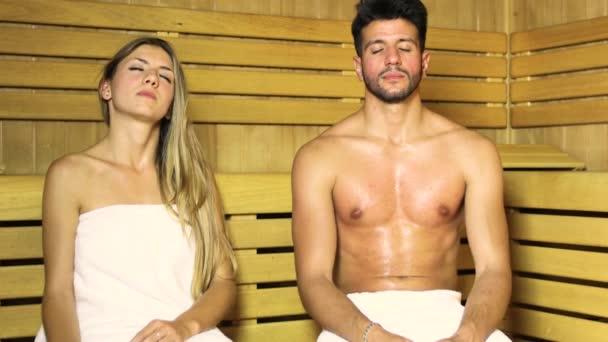 Paar beim Saunabad im Dampfbad mit geschlossenen Augen