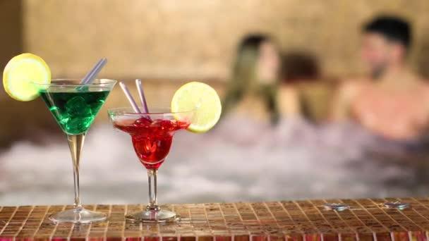 Cocktails und Paar beim Whirlpool-Bad in einem Wellnessbereich im Hintergrund