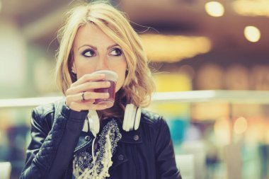 Woman drinking tea in a public place
