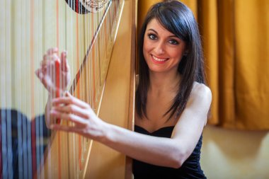 Smiling woman playing an harp