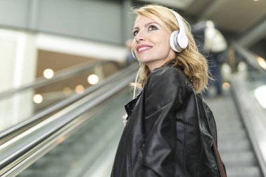 Woman listening music in a shopping mall