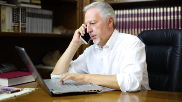 Muž jeho přenosném počítači při telefonování