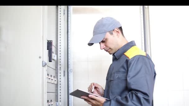 Porträt eines Elektrikers bei der Arbeit mit dem Tablet