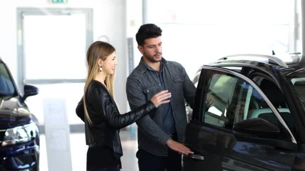 Young couple choosing new car for buying in dealership shop 4k