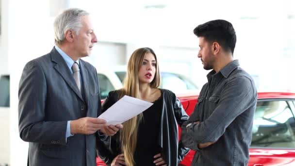 Car dealer reading a contract to a couple in an auto showroom 4k