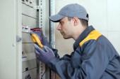 Elettricista sul lavoro usando un tester su un pannello industriale in una fabbrica