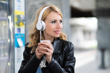 Woman listening to music and drinking coffee