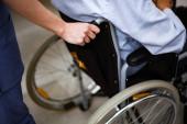Krankenschwester schubst verletzte Patientin im Rollstuhl