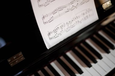 Closeup of a piano keyboard and a music sheet