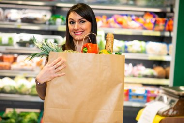 Woman holding an healthy food bag in a grocery store