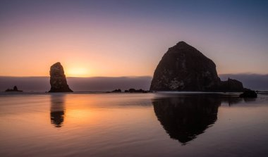 Pacific Coast Sea Stack. Silhouette of sea stacks at sunset with the famous haystack rock at Cannon beach on the Pacific Northwest coastline, Oregon