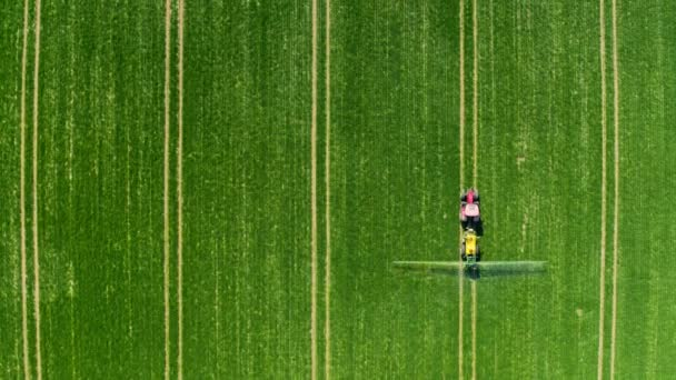 Small tractor spraying the chemicals on the big field in Poland, aerial view