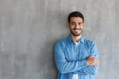 Portrait of smiling handsome man in blue shirt standing with crossed arms against gray textured wall with copy space