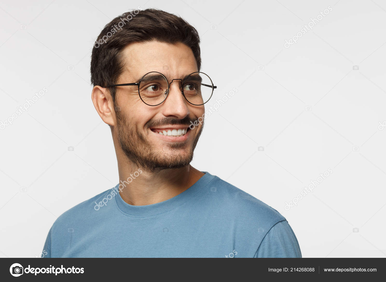 a80fb8de060 Closeup headshot of young man in round eyeglasses isolated on gray  background