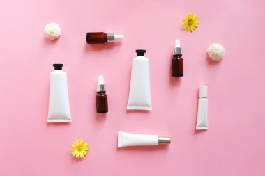 Flat lay of various organic skincare products for mock up in minimal style on pink background
