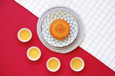 Flat lay of chinese moon cake with hot tea and on table cloth with red background, holiday and festival concept
