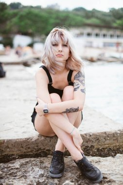 Beautiful young woman with tattoo and black dress posing on sea background