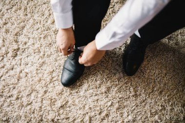 The man wears shoes. Tie the laces on the shoes. Mens style.
