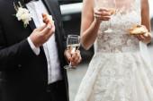 Ženich a nevěsta drží, svatební skleničky