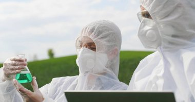 Close up of Caucasian female and male farmers researchers holding test tube with chemicals pesticides and laptop computer in green field. Biologists co-workers working and talking in wheat margin. stock vector