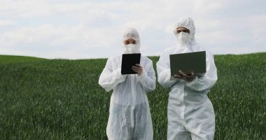 Caucasian male and female scientists in protective costumes standing in green field with tablet device and laptop computer and talking. Man and woman biologist working in margin with harvest. stock vector