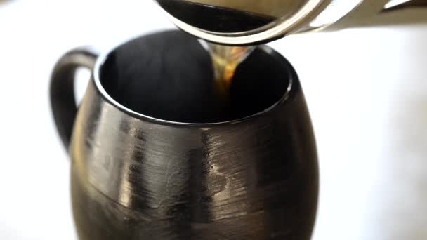 pour coffee into a black cup
