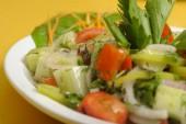 egy fehér tányérra egy sárga táblában friss nyári salátával