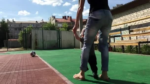 Cute toddler boy holding mothers hand and playing with football ball at playground.