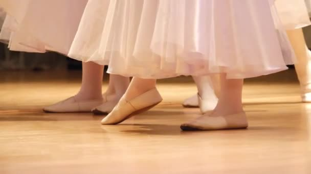 Legs of small artists shod in dance shoes on the stage during the performance.
