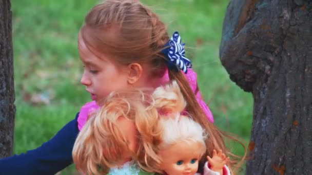 Young girl playing with dolls on outdoors.