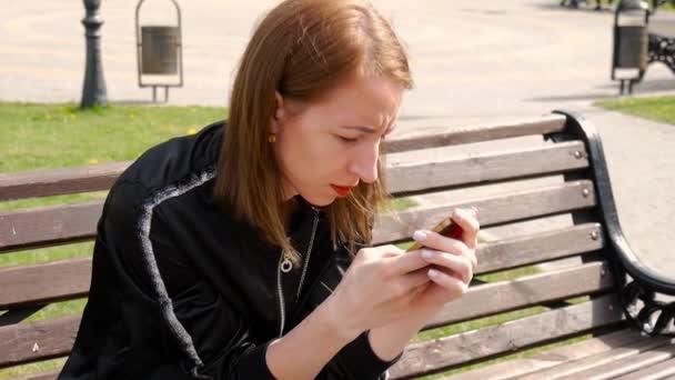Mladá krásná žena vytočit text na mobilním telefonu v parku. Boční pohled na college dívka textových zpráv mobilního telefonu v parku