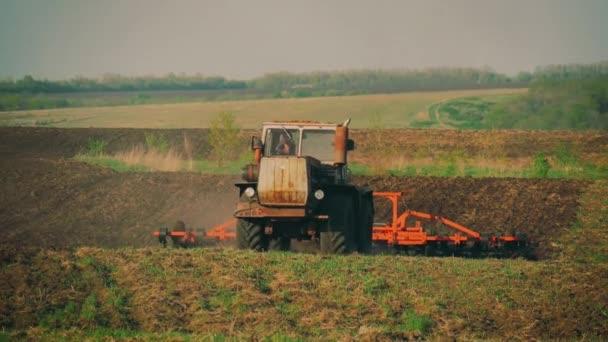 Zemědělský traktor, výsev a pěstování pole. Traktor s přívěsem pluhu orat pole po západu slunce