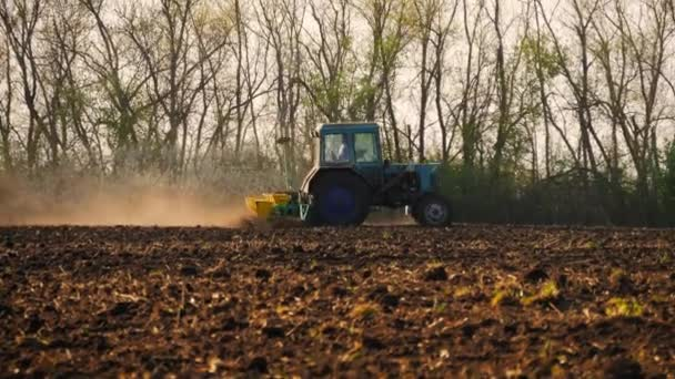 Agricultural tractor sowing and cultivating field. Tractor with a plow trailer plowing the field after sunset.