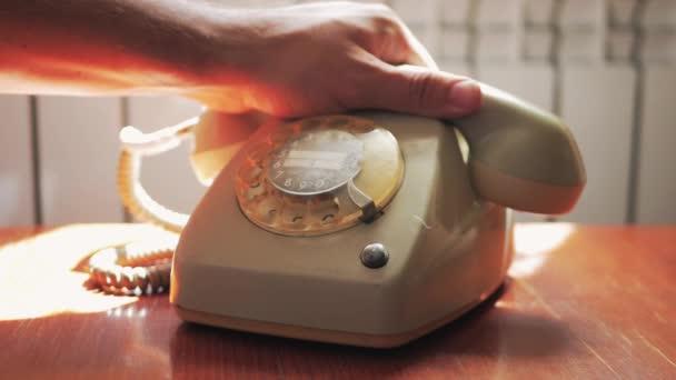 Detailní záběr z mužských rukou zvedl přijímač vintage retro rotační telefon a nezvedá telefon.