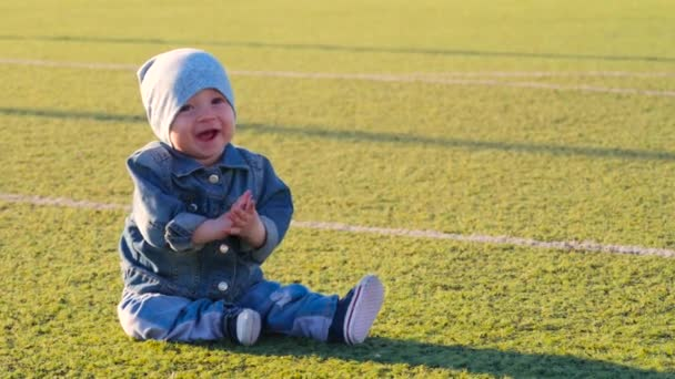 Cute baby boy sitting at football field. Active childhood concept.
